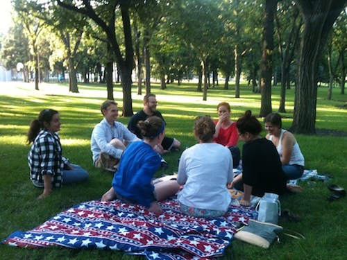 People sitting on a picnic blanket in a park